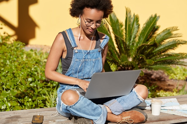 Foto de mujer atractiva con corte de pelo afro, sentada de piernas cruzadas con computadora portátil portátil, nueva publicación de teclados para su blog, escucha música, usa teléfono móvil, auriculares, viste ropa elegante