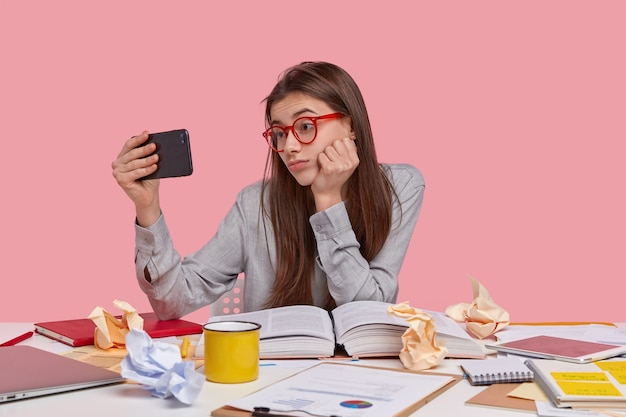 Foto de mujer atractiva sostiene un teléfono celular moderno frente a la cara, hace videollamadas, trabaja como autónomo desde casa, prepara un informe creativo