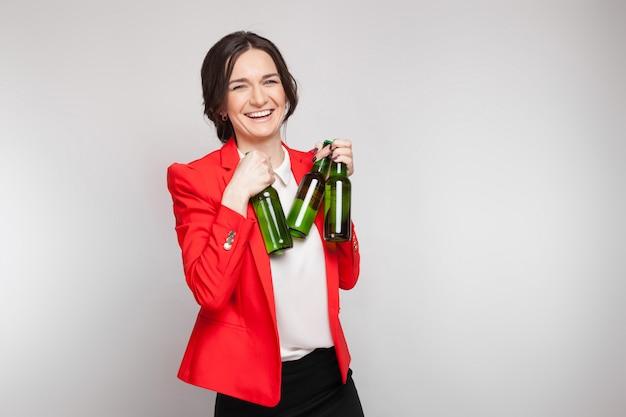 Foto de mujer atractiva en vestido rojo con cerveza verde en manos