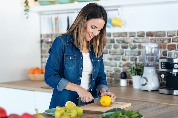Foto de mujer bastante joven cortando limones para preparar bebidas de desintoxicación en la cocina de casa.