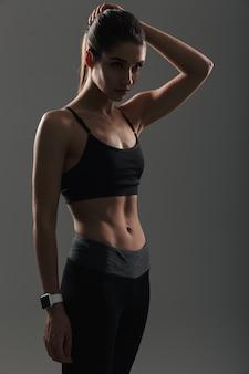 Foto de mujer bonita con cuerpo delgado y musculoso posando en ropa deportiva con cronómetro en la muñeca, aislado sobre la pared oscura