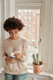 Foto de mujer bonita de piel oscura tiene un descanso para tomar café con un dispositivo moderno, disfruta de la comunicación en línea