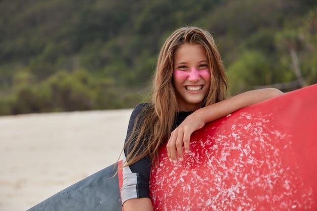 Foto de mujer bonita con zinc de surf para protección facial, sostiene tabla de surf encerada, posa sobre el acantilado