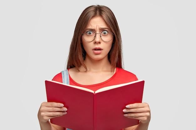 Foto de una mujer caucásica joven emocional estupefacta que mira con estupefacción, sostiene un libro rojo, tiene que aprender mucho para la próxima lección, lleva gafas redondas, aisladas sobre una pared blanca