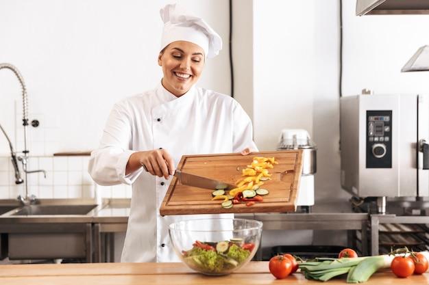 Foto de mujer chef profesional vistiendo uniforme blanco haciendo ensalada con verduras frescas, en la cocina del restaurante