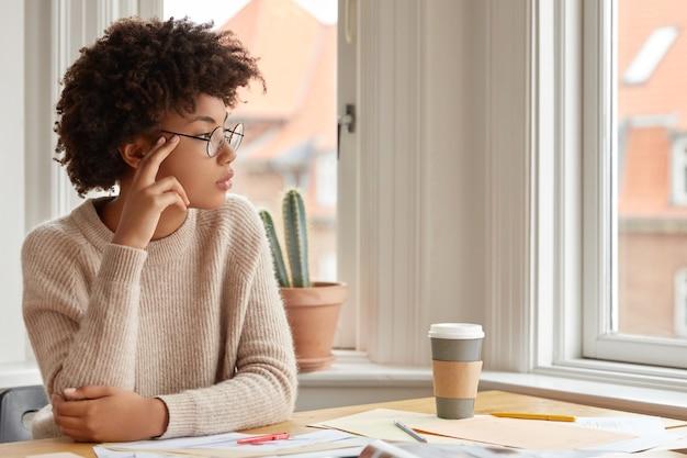 Foto de mujer contemplativa con peinado afro, usa gafas redondas, suéter cálido casual