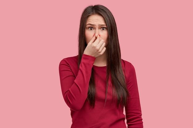 Foto de mujer disgustada que cierra la nariz con hedor, siente un olor terrible a basura, viste ropa roja