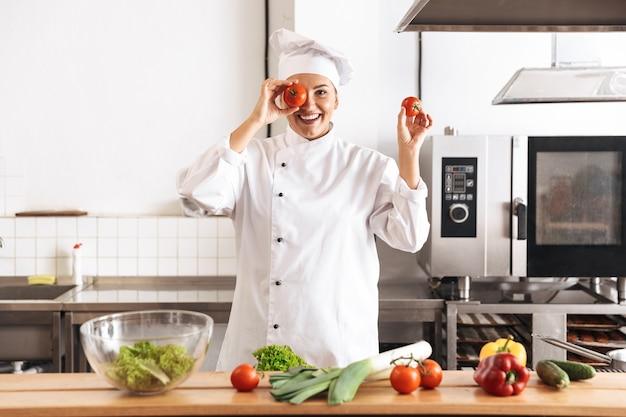 Foto de mujer divertida chef vistiendo uniforme blanco cocinar comida con verduras frescas, en la cocina del restaurante