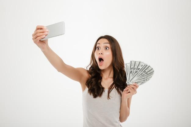 Foto de mujer divertida sorprendida haciendo selfie fotografiando en plata móvil, teléfono mientras sostiene un abanico de billetes de dólar aislado sobre la pared blanca
