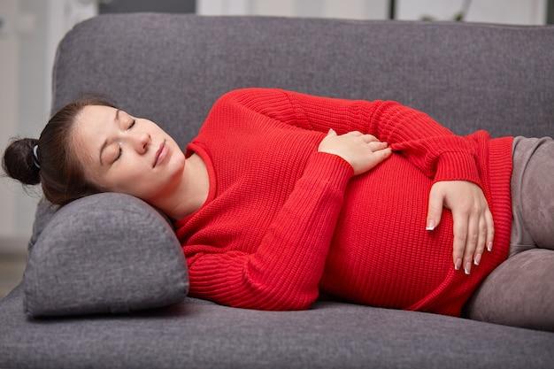 La foto de una mujer embarazada cansada y dormida toma una siesta, mantiene las manos sobre el vientre, usa un suéter rojo cálido, disfruta de un buen descanso en el sofá en casa
