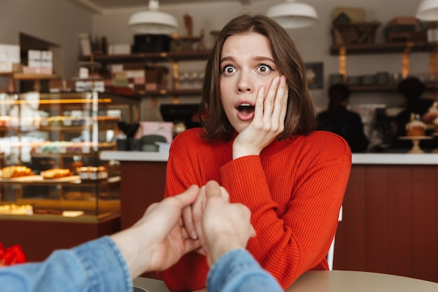 Foto de mujer emocionada expresando sorpresa con la boca abierta, mientras que el hombre sosteniendo su mano con propuesta
