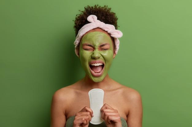 La foto de una mujer emocional de pelo rizado sostiene una toalla sanitaria limpia, tiene períodos o menstruación, se aplica una mascarilla de arcilla para una piel sana, se para en el interior medio desnuda, usa una diadema, exclama con la boca abierta