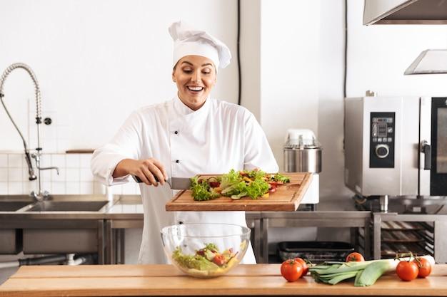 Foto de mujer encantadora jefa con uniforme blanco haciendo ensalada con verduras frescas, en la cocina del restaurante