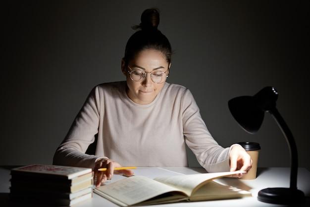 La foto de la mujer enfocada tiene un nudo en el cabello, tiene una expresión seria e inteligente en el libro de texto