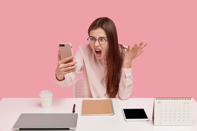 Foto de mujer enojada indignada sostiene un teléfono celular moderno, hace videollamadas, discute con un colega, posa en el lugar de trabajo