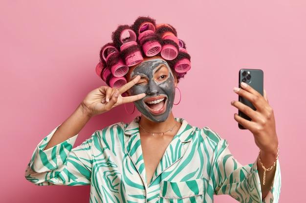 La foto de una mujer étnica complacida hace un gesto de paz sobre los ojos sonríe ampliamente aplica la máscara de belleza los rulos toma un retrato selfie en el teléfono móvil usa una bata aislada sobre una pared rosa