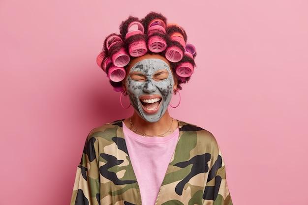 Foto de mujer étnica llena de alegría se ríe a carcajadas fels muy feliz disfruta de tratamientos faciales quiere tener un aspecto fabuloso hace peinado reduce las arrugas con mascarilla de arcilla nutritiva. concepto de belleza