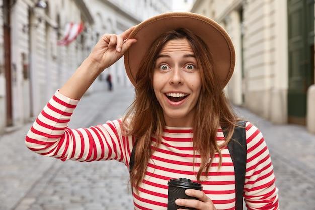 Foto de mujer europea alegre sorprendida mantiene la mano en el sombrero, bebe café para llevar, camina por las calles de la ciudad