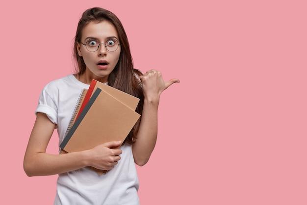 Foto de mujer europea estupefacta con expresión facial conmocionada, conteniendo el aliento, lleva blocs de notas en espiral, señala con el pulgar a un lado