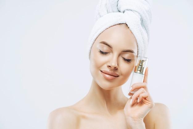Foto de mujer europea joven sana relajada se encuentra con los ojos cerrados, sostiene una botella de producto cosmético para la piel elástica, posa semidesnuda sobre fondo blanco.