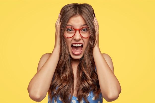 Foto de mujer europea loca con cabello oscuro, mantiene las manos en la cabeza, exclama con locura, se siente irritada