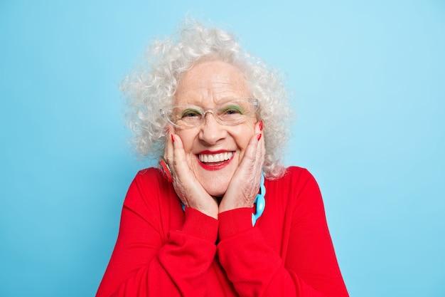 Foto de mujer europea de pelo gris positivo arrugado mantiene las manos en las mejillas sonríe agradablemente