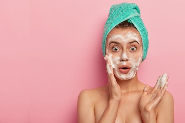 Foto de mujer europea sorprendida que se lava la cara con gel de espuma, quiere tener una piel fresca y bien cuidada, se para en topless, usa una toalla envuelta en el cabello mojado, posa sobre un fondo rosa, espacio libre a un lado