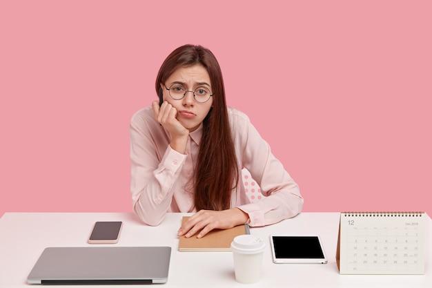 Foto de mujer europea triste sostiene la barbilla, mira descontento, usa gafas redondas y camisa elegante, no quiere trabajar