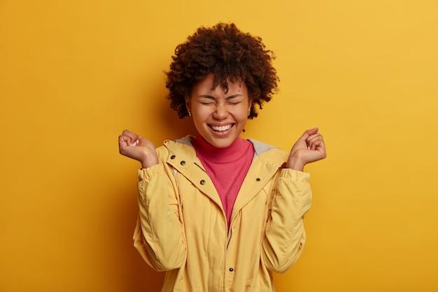 Foto de una mujer exagerada que ve comedia, se ríe alegremente con los puños cerrados, se siente entretenida y se divierte, mantiene los ojos cerrados, aplaude puntuación excelente