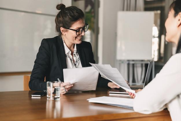 Foto de mujer exitosa sosteniendo currículum vitae y negociando con candidata durante una reunión corporativa o entrevista de trabajo - concepto de negocio, carrera y colocación