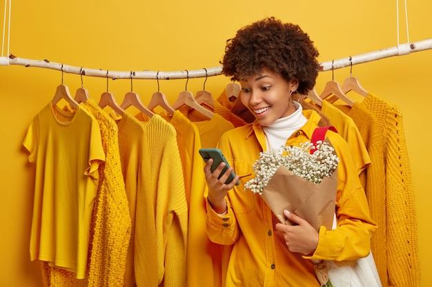 Foto de mujer feliz se viste para la primera cita, se para cerca del perchero de la ropa, recibe sms agradables en el teléfono inteligente, sostiene un hermoso ramo