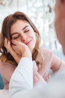 Foto de mujer gentil con los ojos cerrados disfrutando cuando sostiene la mano masculina en su rostro, mientras tiene cita en el restaurante