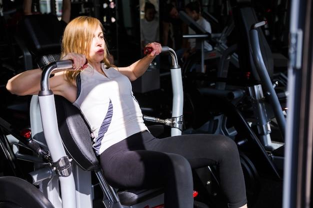 Foto de mujer en el gimnasio haciendo ejercicio de brazos con máquina de ejercicios