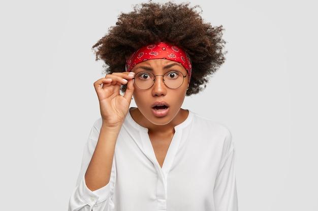 Foto de mujer hermosa aterrorizada mantiene la mano en el borde de las gafas