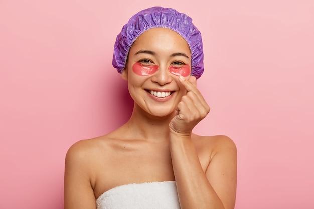 La foto de una mujer hermosa hace un signo de mano coreano, expresa amor, muestra el gesto del corazón con el dedo, usa gorro de baño, se para envuelto en una toalla, aplica parches cosméticos en los ojos, sonríe feliz.