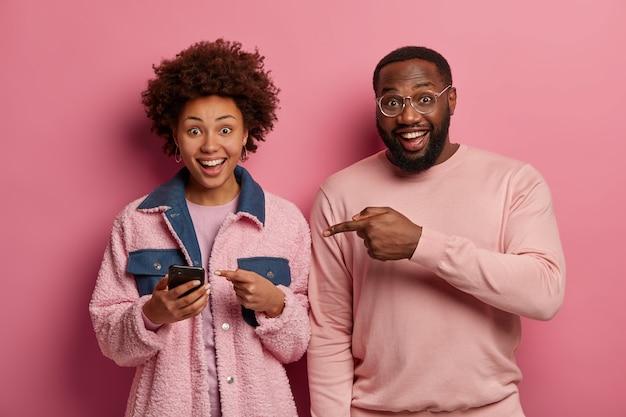 La foto de la mujer y el hombre alegres señalan el dispositivo del teléfono inteligente, miran contenido de video interesante, se colocan uno al lado del otro, sonríen ampliamente
