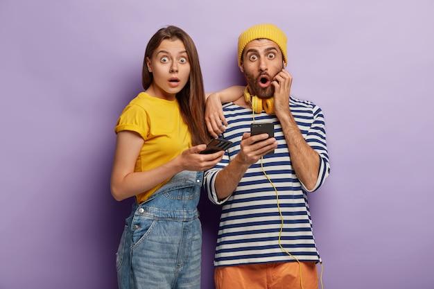 Foto de una mujer y un hombre asustados posan con teléfonos móviles, conmocionados con noticias asombrosas, desconcertados con actualizaciones inesperadas, temerosos de algo