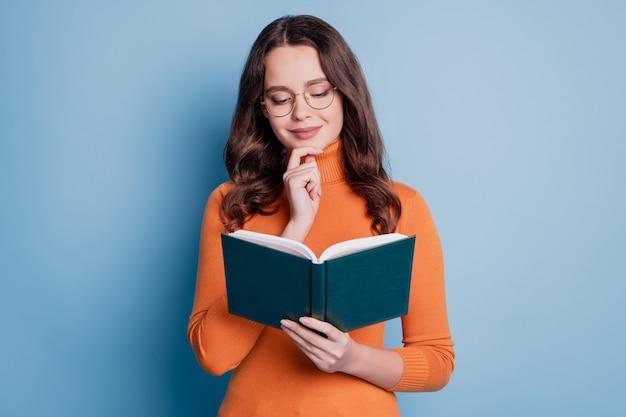 Foto de mujer inteligente leer libro dedo barbilla soñar imaginar sobre fondo azul.
