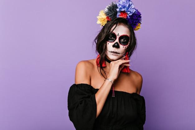 Foto de mujer inusual en traje de bruja. chica con cabello oscuro y rizado toca la cara pintada.