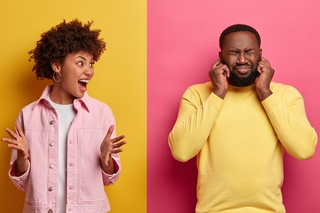 Foto de mujer irritada grita con emociones negativas, gesticula con enojo y le grita al esposo que se tapa los oídos e ignora los gritos de las esposas
