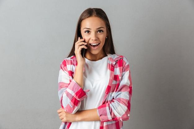 Foto de mujer joven alegre, hablando por teléfono celular