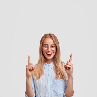 Foto de mujer joven alegre y linda con una sonrisa suave, indica hacia arriba con ambos dedos índices, muestra algo por encima de la cabeza, usa una camisa elegante y gafas, aislado sobre una pared blanca