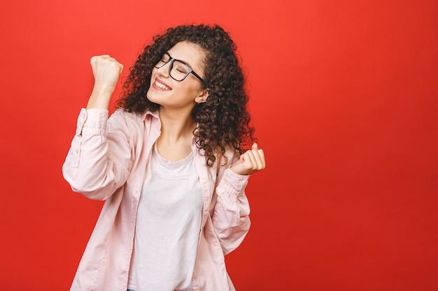 Foto de la mujer joven alegre que se coloca aislada sobre fondo rojo de la pared. mirando la cámara mostrando gesto ganador.
