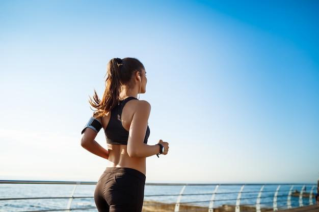 Foto de mujer joven atractiva fitness trotar con mar en la pared