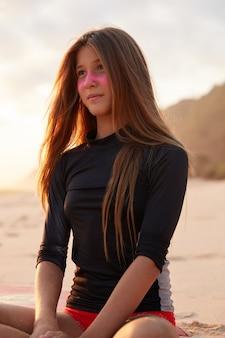 Foto de mujer joven y bonita de ensueño vestida con traje de baño, tiene máscara de zinc rosa, se sienta con las piernas cruzadas en la playa, piensa en algo, se enfoca en la distancia personas, estilo de vida y concepto de deporte extremo.