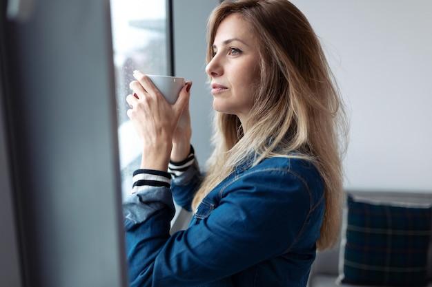 Foto de mujer joven y bonita mirando por la ventana mientras toma café en la sala de estar en casa.