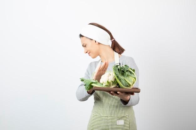 Foto de una mujer joven en delantal sosteniendo una placa de madera con coliflores