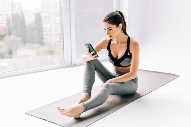 Foto de mujer joven deportiva usando su teléfono móvil mientras está sentado en casa