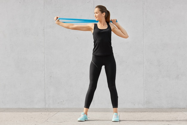 Foto de mujer joven deportiva vestida de negro, estira las manos con goma de mascar, quiere tener músculos, tiene buena flexibilidad