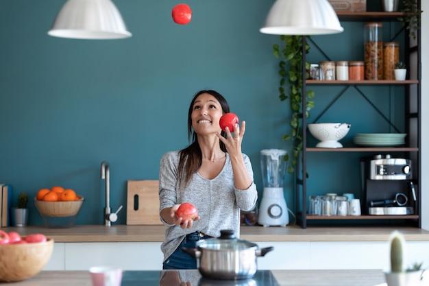 Foto de mujer joven divertida haciendo malabares con tres manzanas rojas en la cocina de casa.